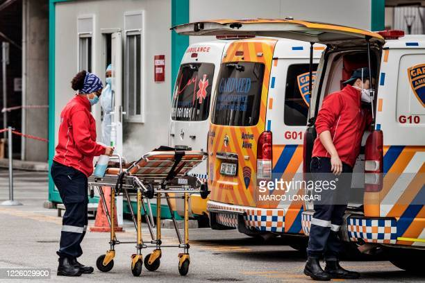 Member of an ambulance crew sanitises a gurney at the emergencies of the Greenacres Hospital in Port Elizabeth, on July 10, 2020 near a line of...