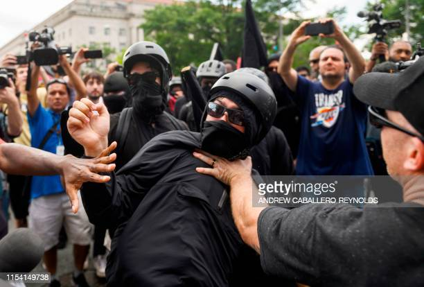 A member of an antifascist or Antifa group is held back while he argues with a Trump supporter as the AltRight movement gathers for a Demand Free...