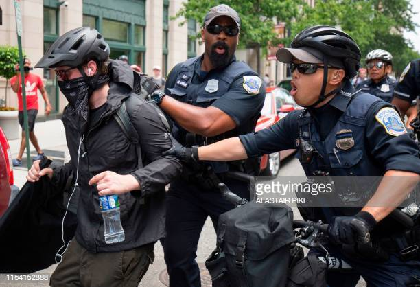 A member of an antifascist or Antifa group is pushed by police as the AltRight holds a Demand Free Speech rally in Washington DC July 6 2019