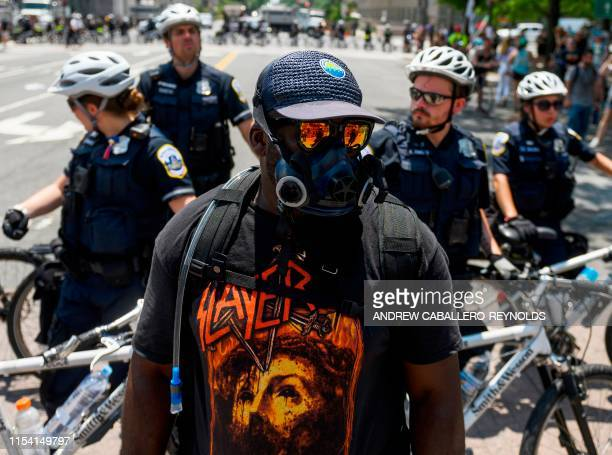 A member of an antifascist or Antifa group stands in front of police as the AltRight movement gathers for a Demand Free Speech rally in Washington DC...