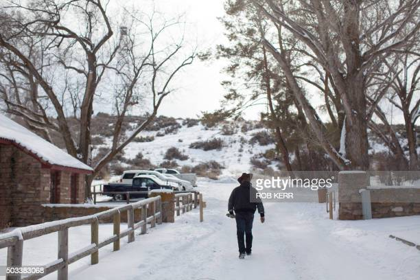 A member of an armed antigovernment militia walks down a road January 4 2016 at the Malheur National Wildlife Refuge Headquarters near Burns Oregon...