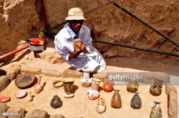A member of an Egyptian archaeological team shows artifacts discovered in a 3500yearold tomb in the Draa Abul Nagaa necropolis near the southern city...