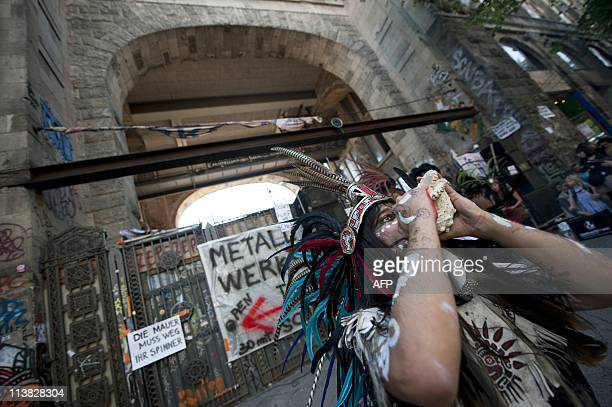 A member of an Indian dance group from South America performs in front of the Tacheles artist colony during a demonstration to support the...