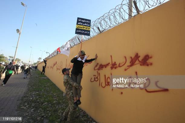 Member of an Iraqi Shiite paramilitary group helps a fellow protesters holding a placard denouncing the United States climb on the outer wall of the...