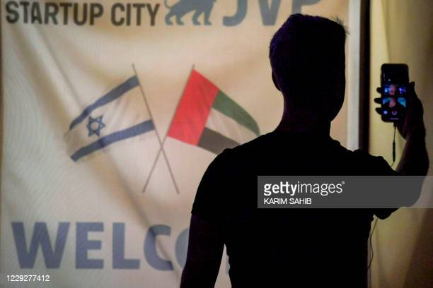 Member of an Israeli tech delegation uses his phone in a video call during an evening meeting with Emirati counterparts at a hotel in Dubai on...