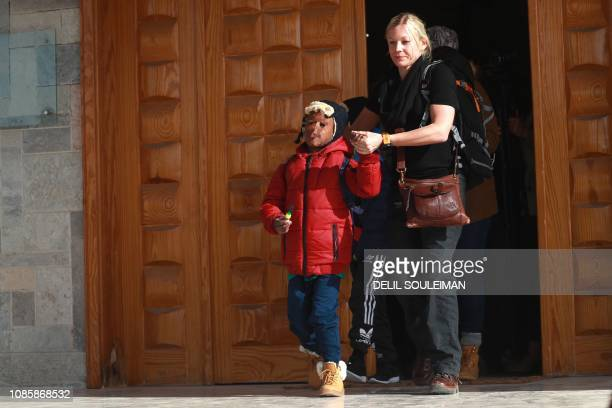 Member of an NGO accompanies two Caribbean children as they prepare to leave the northeastern Syrian Kurdish-majority city of Qamishli on January 21,...