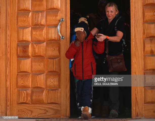 A member of an NGO accompanies two Caribbean children as they prepare to leave the northeastern Syrian Kurdishmajority city of Qamishli on January 21...