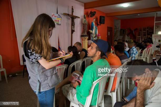 A member of an NGO informs to Venezuelan people about the procedures for their stay in the country at the church of San Nicolás on August 17 2018 in...