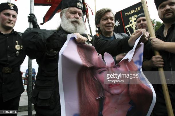 A member of an Orthodox nationalist group tears in half a poster of US pop singer Madonna in protest of her upcoming concert in Moscow in Pushkin...