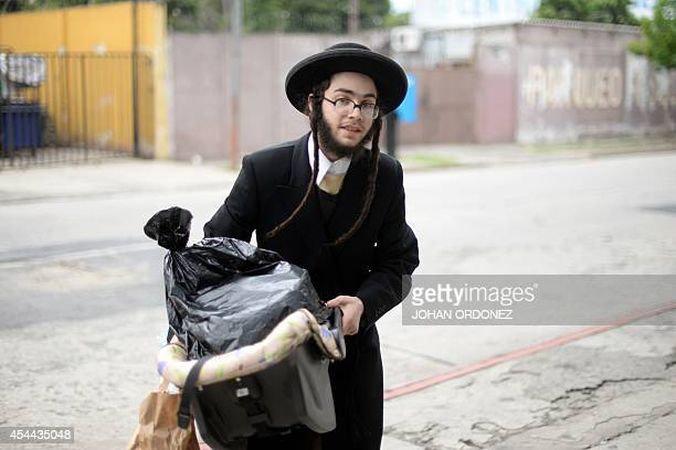 A member of an ultraOrthodox Jewish group arrives at the building where he will remain with his community in Guatemala City on August 31 2014 Fearful...