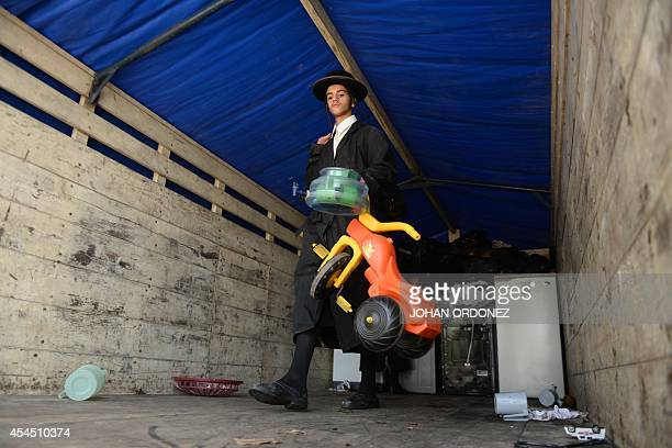A member of an ultraOrthodox Jewish group unloads belongings from a truck as he arrives to the building where the group will remain in Guatemala City...