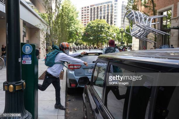 A member of Antifa throws cafe chairs into the street in front of police during counterprotests against the Patriot Prayer Rally The Proud Boys...