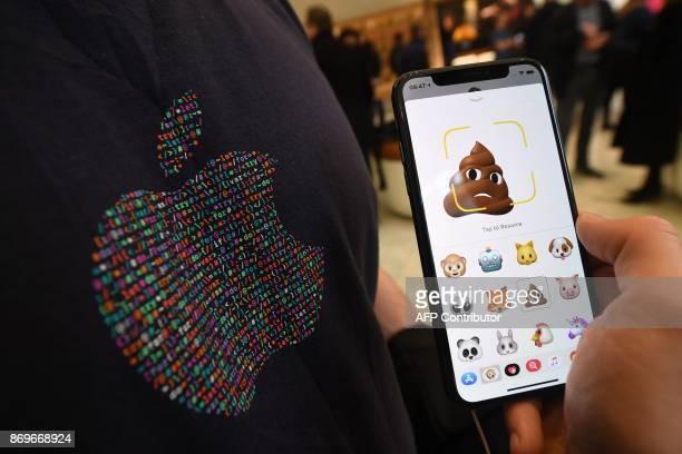 A member of Apple staff pose with a new Apple iPhone X smartphone showing new emoji features in Apple's Regent Street store in central London on...