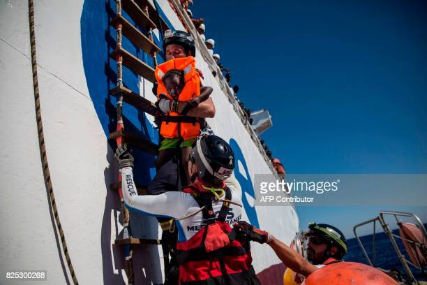 A member of Aquarius rescue ship run by NGO SOS Mediterranee and Medecins Sans Frontieres holds a girl after she was recovered with others by Santa...