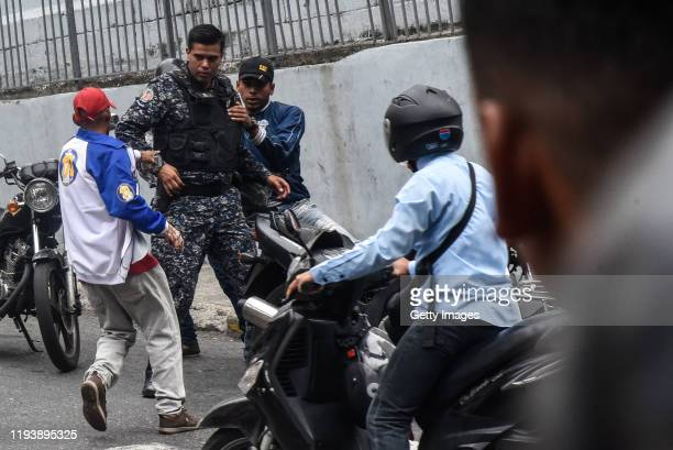 A member of armed groups that support the government called Colectivos runs to attack a media worker that attempts to hide behind a member of the...