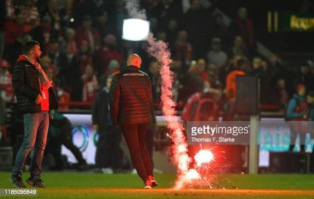 Member of backroom staff of 1. FC Union Berlin avoids a flare which lands on the pitch during the Bundesliga match between 1. FC Union Berlin and...