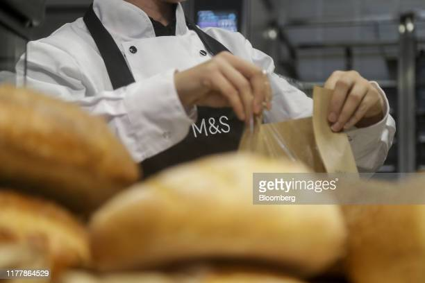 A member of bakery staff packages fresh bread at Marks and Spencer Group Plc's newly opened store in Fraddon UK on Wednesday Oct 23 2019 Marks...