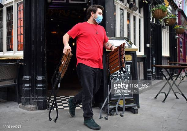 Member of bar staff puts the outdoor seating in place as the pub opens in the Soho district of London on October 18 as further restrictions come into...