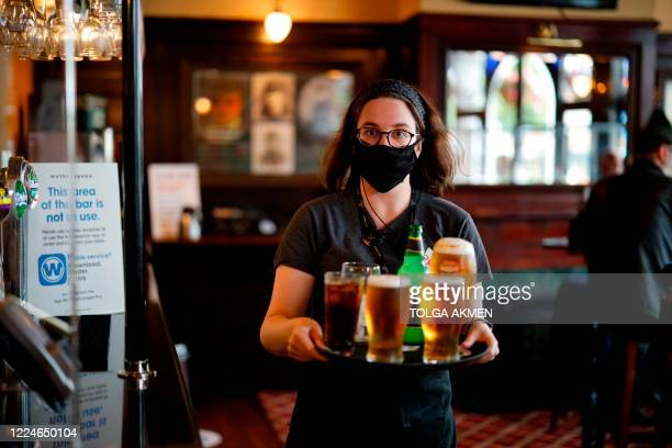Member of bar staff wearing PPE in the form of a face mask, carries drinks inside the Wetherspoon pub, Goldengrove in Stratford in east London on...