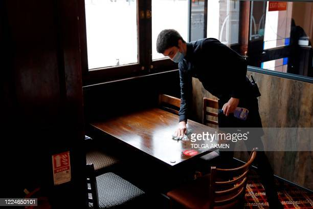 Member of bar staff wearing PPE in the form of a face mask, cleans a table inside the Wetherspoon pub, Goldengrove in Stratford in east London on...