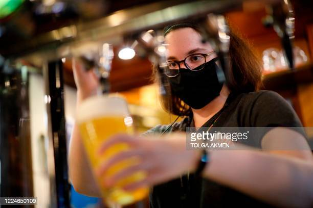 A member of bar staff wearing PPE in the form of a face mask pours drinks inside the Wetherspoon pub Goldengrove in Stratford in east London on July...