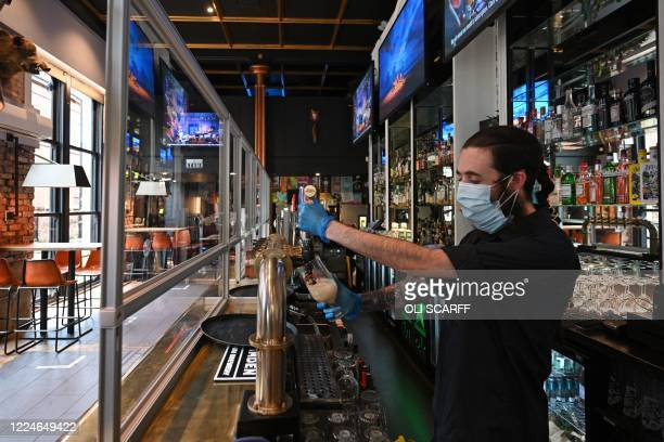 Member of bar staff wearing protective gloves and a face covering pours a drink behind a perspex barrier in The Brotherhood of Pursuits and Pastimes...
