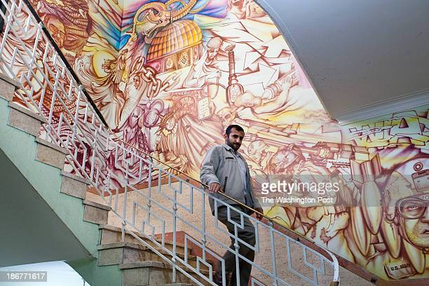 Member of Basij steeping down the stairs and passing through the interior walls of the former U.S embassy in Tehran that filled with anti-U.S...
