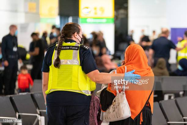 Member of Border Force staff assists a female evacuee as refugees arrive from Afghanistan at Heathrow Airport on August 26, 2021 in London, England....