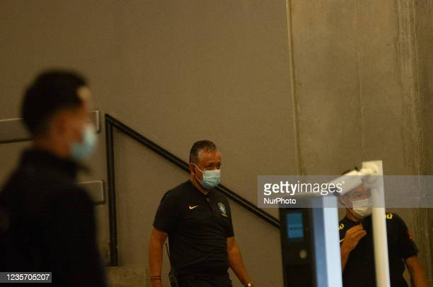Member of Brazil's national team tecnical comission boards a bus as members of the Brazil federation of football team board their bus at the Grand...