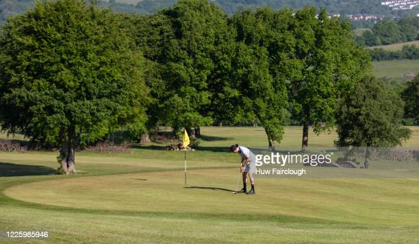 A member of Bryn Meadows Golf Course prepares his putt as restrictions on playing golf in Wales have been eased but still differ to golf in England...