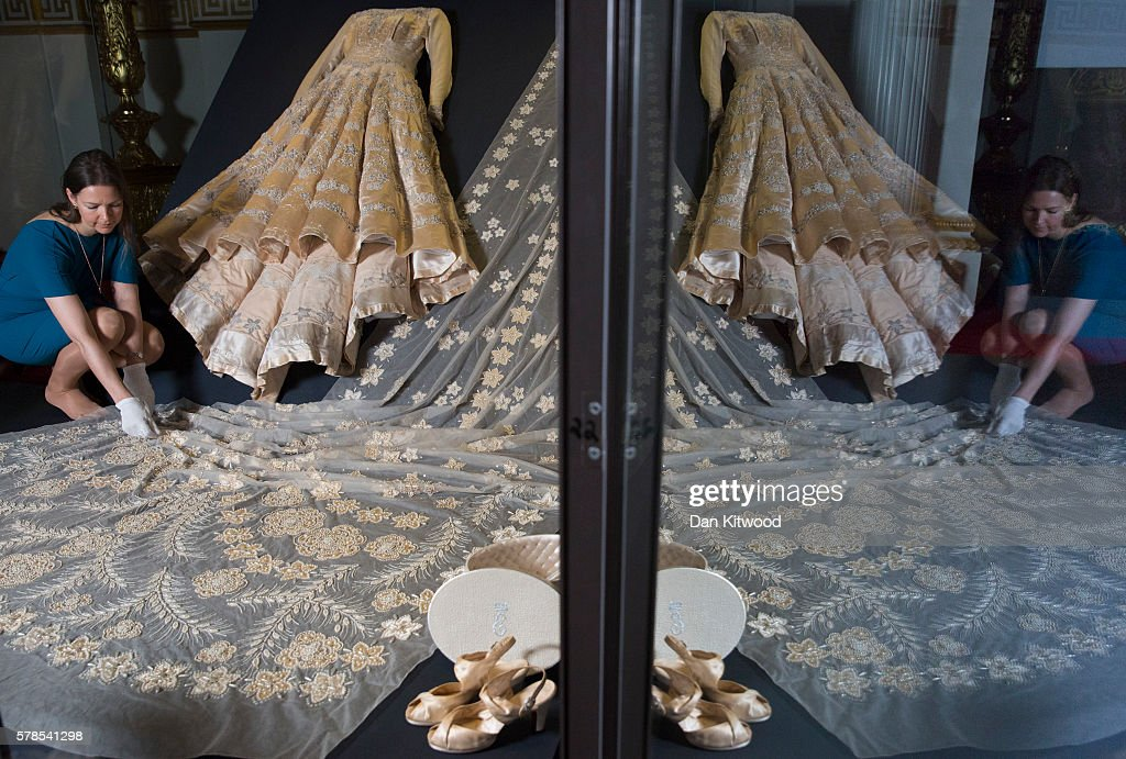 A member of Buckingham Palace staff poses inside a glass case containing Queen Elizabeth II's wedding dress during a photocall at Buckingham Palace on July 21, 2016 in London, England. The dress makes up part of a forthcoming exhibit 'Fashioning a Reign: 90 Years of Style from The Queen's Wardrobe' to coincide with the Summer Opening of Buckingham Palace. The exhibit includes outfits worn by the Queen from State events to family celebrations and runs until October 2, 2016.