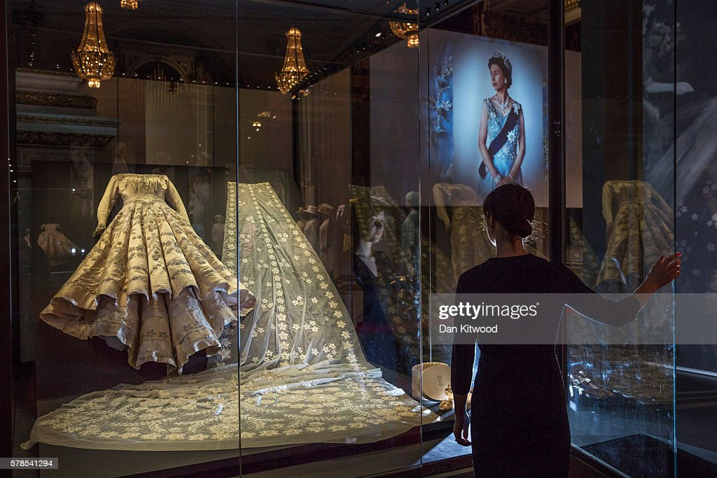 A member of Buckingham Palace staff stands next to a glass case containing Queen Elizabeth II's wedding dress during a photocall at Buckingham Palace on July 21, 2016 in London, England. The dress makes up part of a forthcoming exhibit 'Fashioning a Reign: 90 Years of Style from The Queen's Wardrobe' to coincide with the Summer Opening of Buckingham Palace. The exhibit includes outfits worn by the Queen from State events to family celebrations and runs until October 2, 2016.