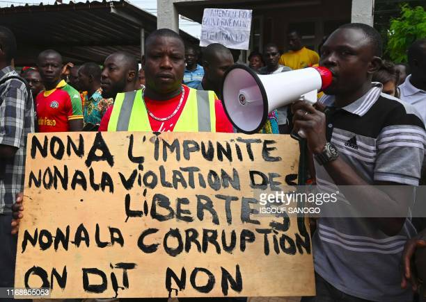 """Member of Burkinabe workers' unions and civil society associations holds a placard readign """"No to impunity - No to violation of liberties - No to..."""