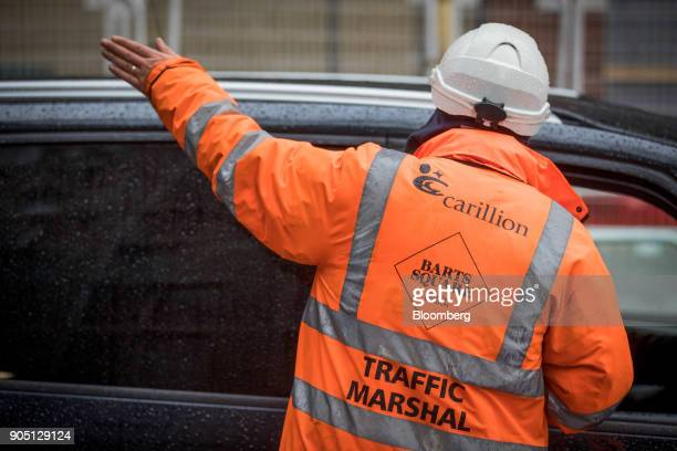 A member of Carillion's staff directs traffic as subcontractors collect their tools on the Barts Square development operated by Carillion Plc in...