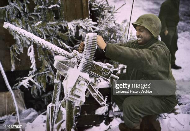 Member of Cavalry Reconnaissance Squadron Checks 30caliber Machine Gun ArdennesAlsace Campaign Battle of the Bulge 1945
