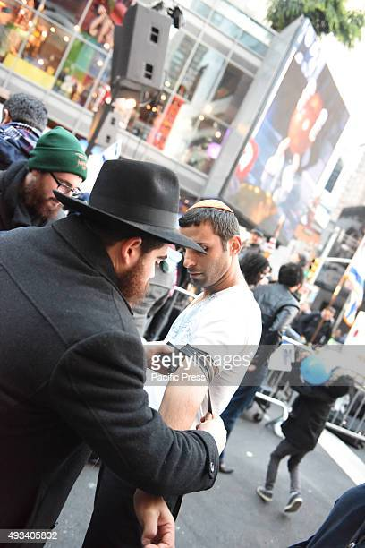 Member of Chabad Lubavitch helps rally attendee with tefilin Several hundred people listened to speeches and songs during a solidarity with Israel...