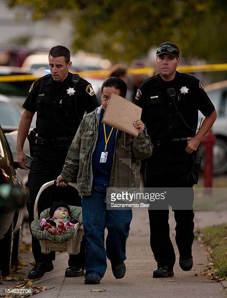 Member of child protection services carries an unharmed 6-month-old boy found at the scene of a triple homicide in a duplex in Rancho Cordova,...