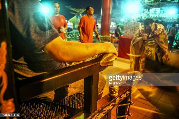 Member of chinese seat on special chair with full of nails as he offer a prayer during hungry ghost festival in Teluk Pulai Klang, Malaysia on...