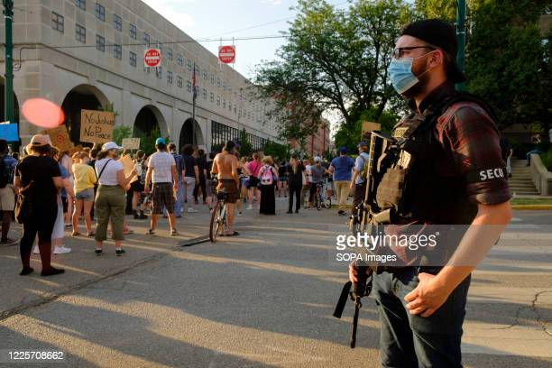 """Member of """"Citizens Protest Response and Safety,"""" holds an AR style rifle at the Monroe County Courthouse during the demonstration against racism...."""
