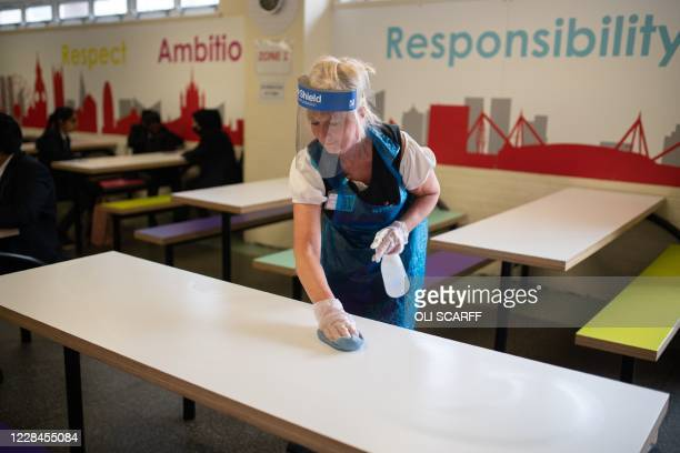 A member of cleaning staff wearing PPE sanitises tables and chairs as a precaution against the transmission of the novel coronavirus in the dining...