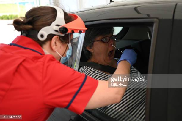 A member of clinical staff wears Personal Protective Equipment as she takes a swab to test a key worker for the novel coronavirus at Royal Papworth...
