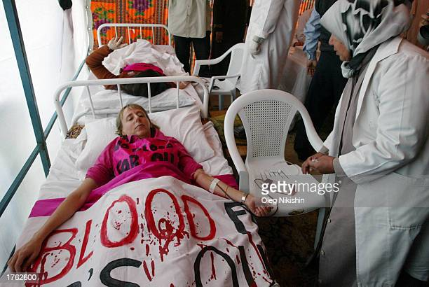 A member of 'CodePink' Women's Peace Group Medea Benjamin of California gives blood as she participates in a peace vigil at AlDoura oil refinery...