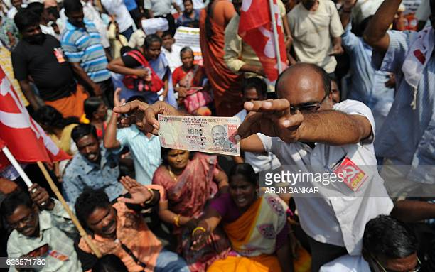 TOPSHOT A member of Communist Party of India displays a 1000 rupees note at a protest against Indian Prime Minister Narendra Modi and the withdrawal...