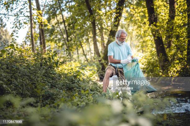 member of community outreach picking up trash in public park - environmentalist stock pictures, royalty-free photos & images