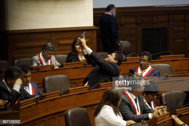 A member of congress uses a mobile device to take a 'selfie' photograph before Martin Vizcarra Peru's president center is sworn into office during a...