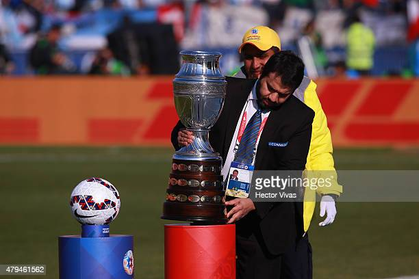 A member of Conmebol places the Copa America trophy on the plinth next to the official matchball Cachaña during the 2015 Copa America Chile Final...