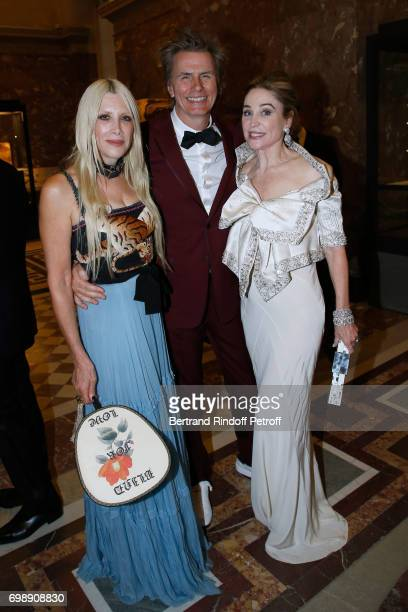 Member of Duran Duran John Taylor standing between his wife Gela and Becca Cason Thrash attend the Liaisons au Louvre IV Evening of patronage for the...