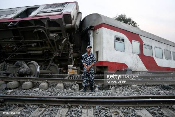 Member of Egyptian security forces stands guard before an overturned passenger carriage at the scene of a railway accident in the city of Toukh in...