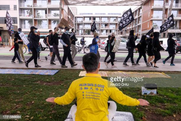 Member of Falun Kung meditates as local natives of Hong Kong walk past during a flash mob march to show solidarity with the 47 pro-democracy...
