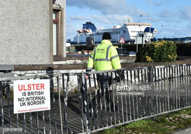 Member of ferry staff walks past a unionist sign erected opposite the harbour entrance on February 10, 2021 in Larne, Northern Ireland. Port...